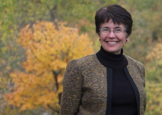 Image of Emmaus CEO Karen Jacobsen in front of fall leaves.
