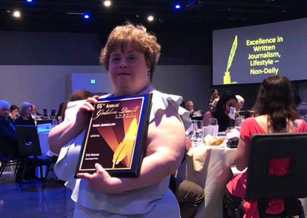 Image of Emmaus resident Erin Gannon holding up Golden Quill award at reception.