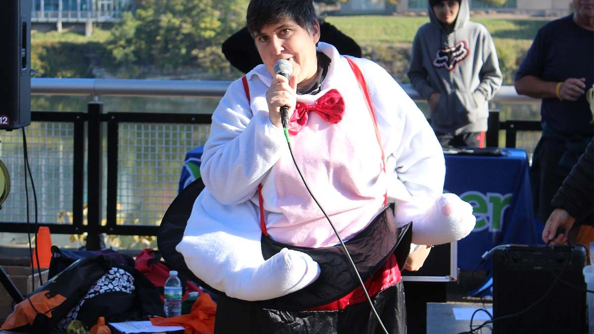Image of Emmaus resident Cece Wagner in magician's costume, performing magic in front of a crowd.