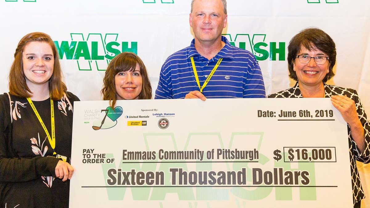 Image of Emmaus staff members and WALSH executive receiving benefit check.