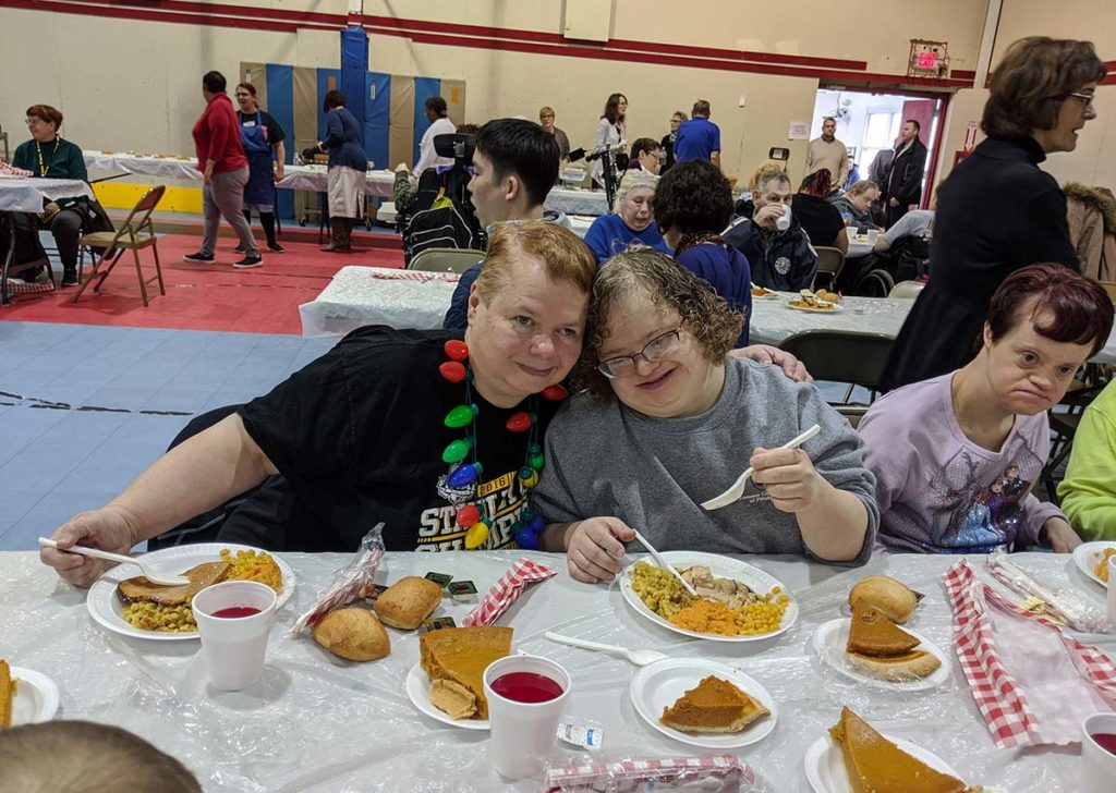 Image of Emmaus residents Amy and Gina at church Thanksgiving feast.