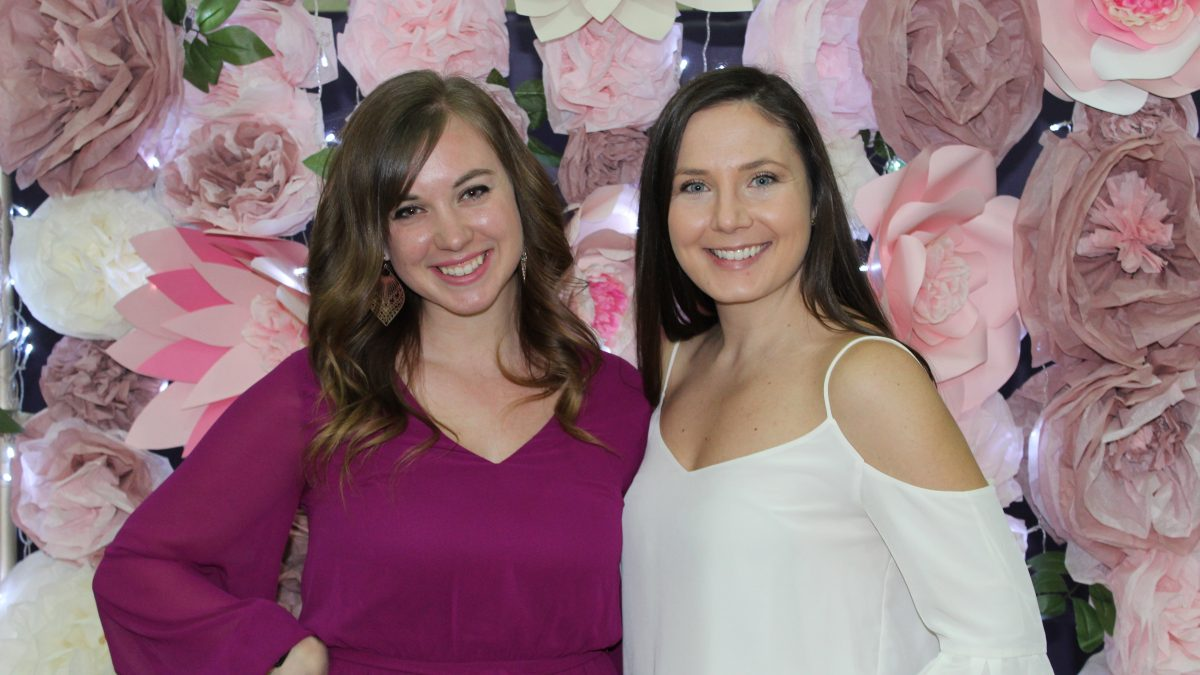 Image of two Purse bash guests in front of flower background.