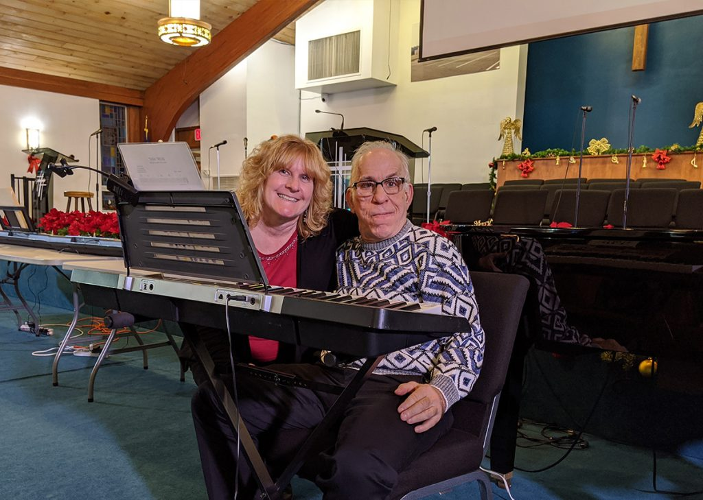 Image of an Emmaus residents and DSP sitting at an instrumental keyboard.